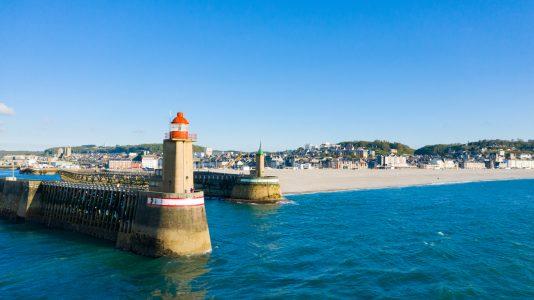 Cette photo a été prise en France, au nord de la Normandie, à Fécamp avec un drone. On y voit l'entrée du port de Fécamp au coucher du Soleil et une grande partie de la plage et de la ville en arrière plan.